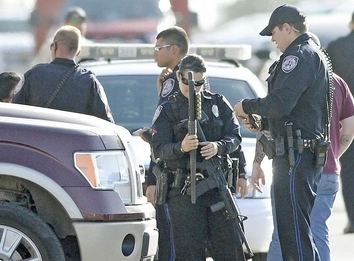 Midland police officers look over a shotgun and a pistol recovered from a crime scene after responding to a domestic disturbance at the Waterford Lakes apartments Tuesday, July 14, 2015. One subject was brought into custody with assistance from a police canine. Two of the subjects involved are being investigated for other crimes throughout the Permian Basin. James Durbin/Reporter-Telegram