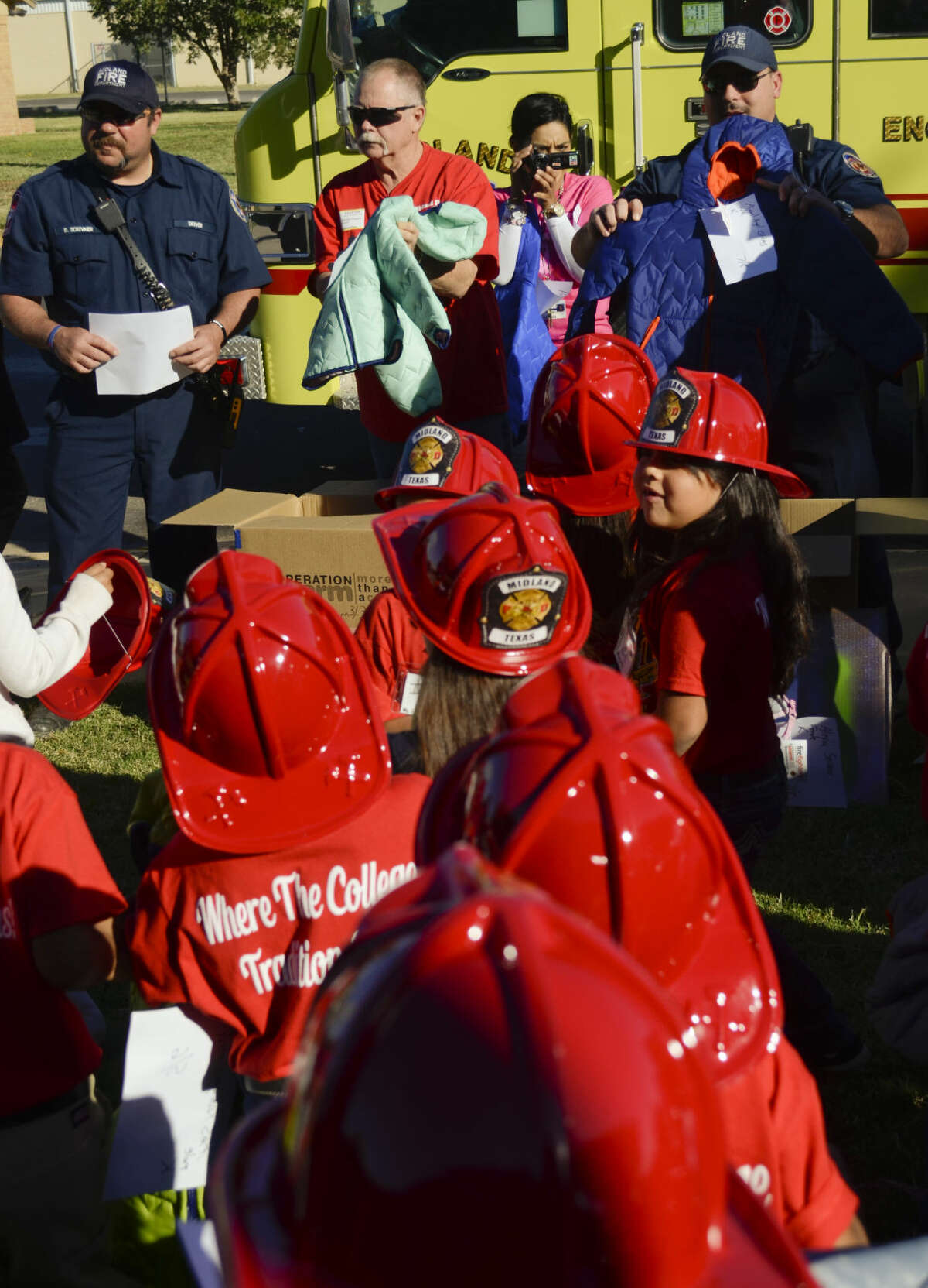 In this 2014 file photo, Midland firefighters Dubby Scrivner, Cliff Hogan and Jeff Coleman help hand out new winter coats to children at South Elementary. Members of the Professional Firefighters Association gave out more than 185 new coats to all children at South Elementary in k-2. Tim Fischer\Reporter-Telegram Tim Fischer\Reporter-Telegram