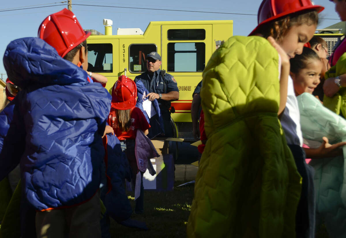 In this 2014 file photo, Midland firefighter Jeff Coleman helps hand out new winter coats to children at South Elementary. Members of the Professional Firefighters Association gave out more than 185 new coats to all children at South Elementary in k-2. Tim Fischer\Reporter-Telegram