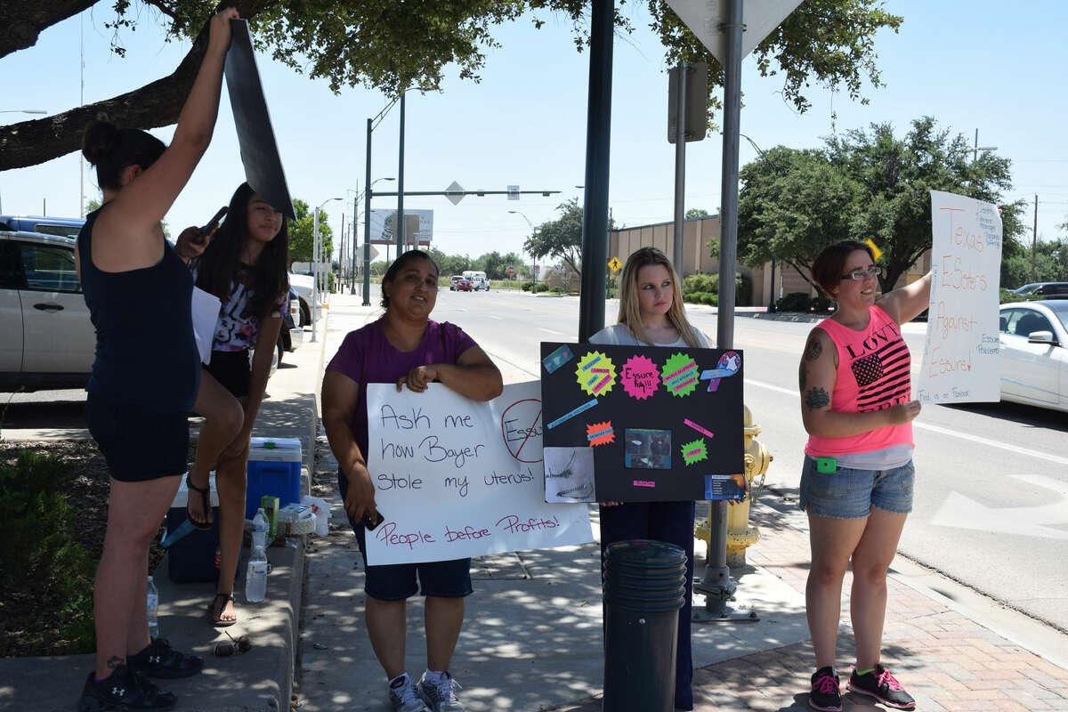 Cecilia Porras, from left, Elvira Lopez, Jordan Leininger and Kristen Jones stand in front of the Midland federal courthouse Wednesday to protest against the Essure IUD.