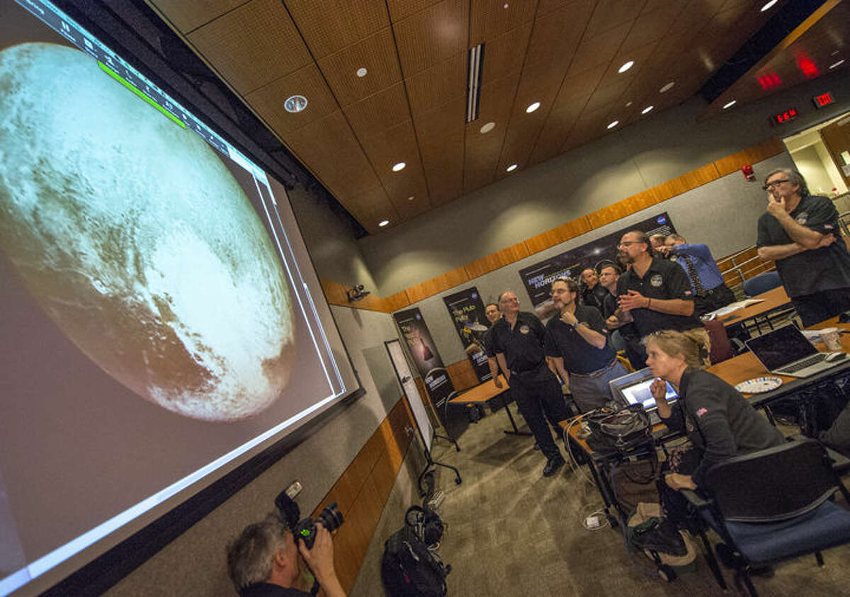 Members of the New Horizons science team reacttoseeing thespacecraft'slast and sharpestimage of Pluto before closest approach later in the day, Tuesday, July 14, 2015, at the Johns Hopkins University Applied Physics Laboratory in Laurel, Maryland.