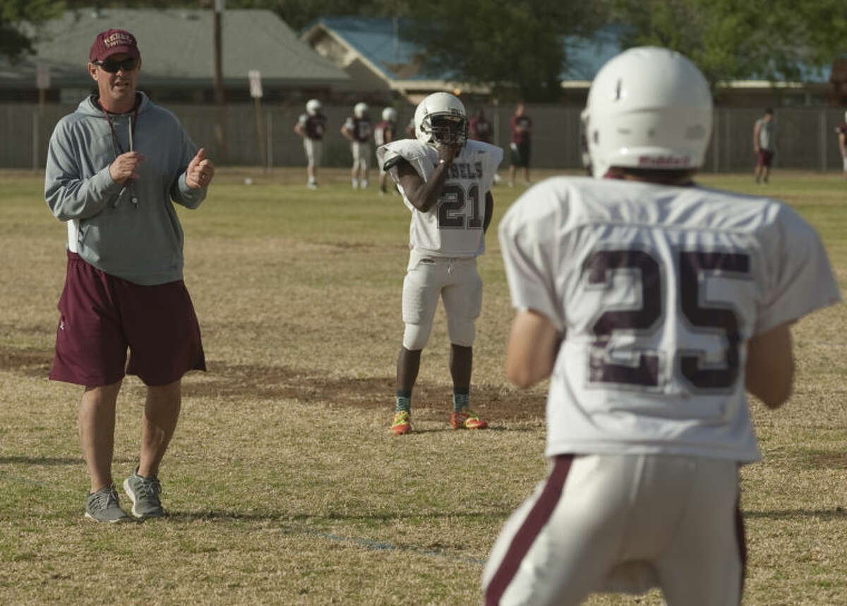 Lee High coach James Mortonworks with his players as they run drills Tuesday on the first day of Spring football practice. Tim Fischer\Reporter-Telegram