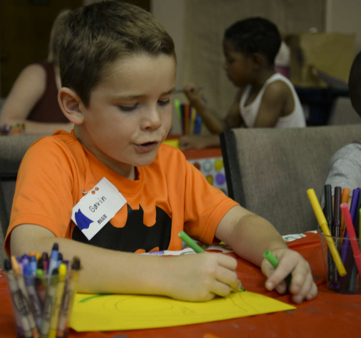 Gavin and others color their super hero shields Wednesday 7-8-15, during crafts at We Are the World Camp. Tim Fischer\Reporter-Telegram