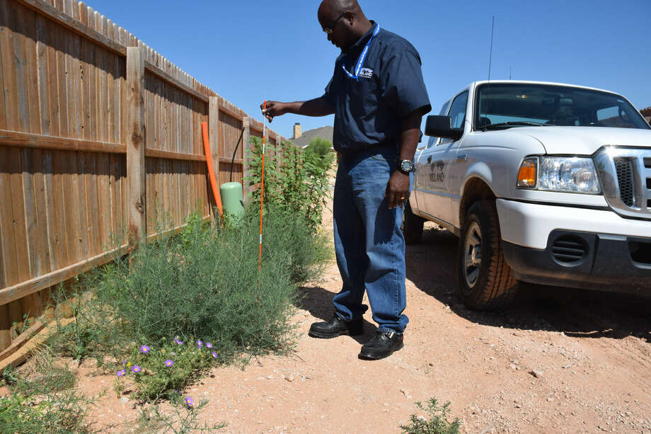 Code compliance officer Rod Shields measures a weed above 18 inches. He says the Legends area is a problem zone when it comes to tall grasses and weeds in alleys. Erin Stone/Reporter-Telegram