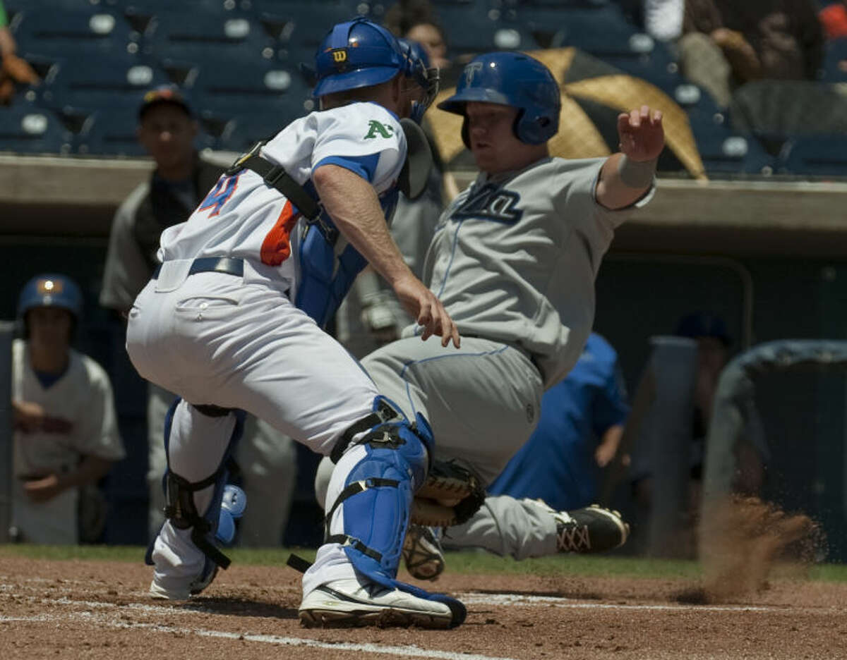 RockHounds' catcher Blake Forsthe appears to make the tag on Drillers' Jared Simon but is called safe Monday at home plate on a three run triple. Tim Fischer\Reporter-Telegram
