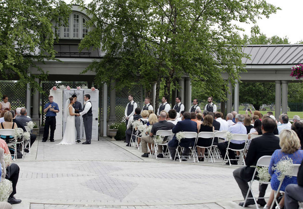 In this June 19, 2015 photo, Danessa Molinder and Billy Castrodale get married in the open air courtyard at the Community Life Center, in Indianapolis, which sits on cemetery land near a funeral home.