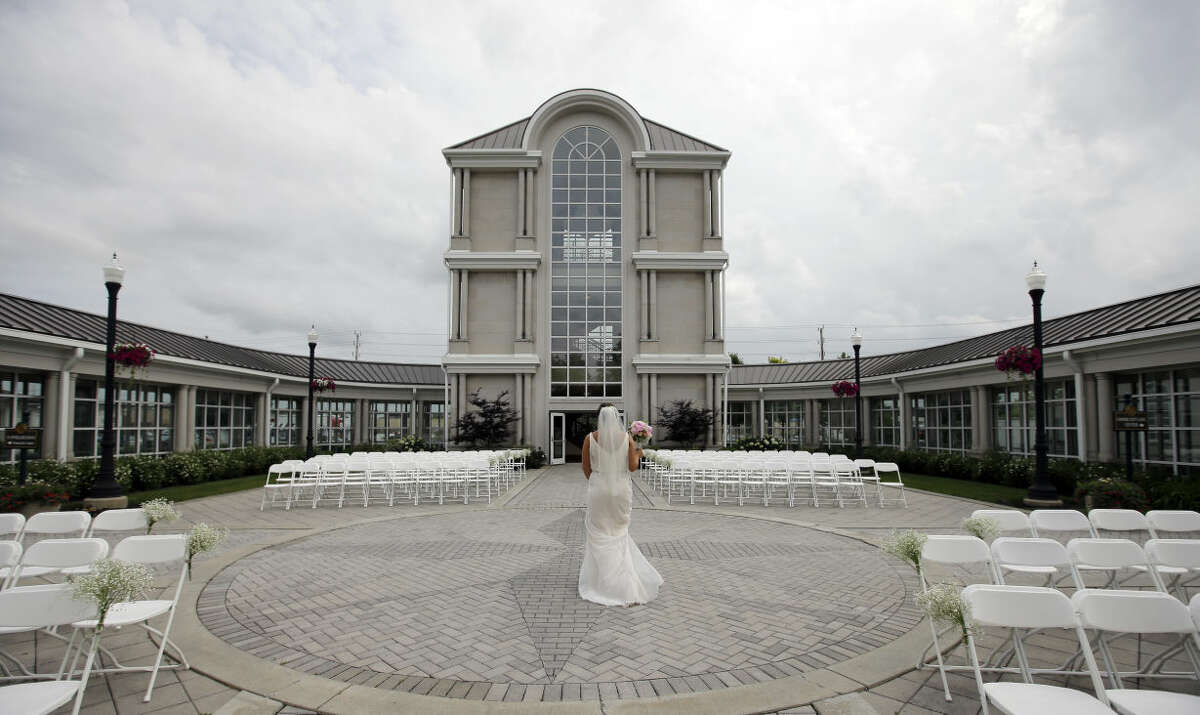 In this June 19, 2015 photo, Danessa Molinder walks towards the Crystal Tower for photos before her wedding at the Community Life Center, in Indianapolis.