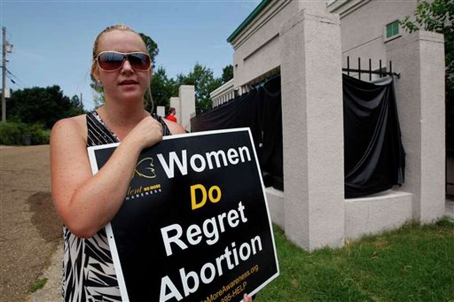In this July 2, 2012 photo, abortion opponent Ashley Sigrest of Brandon, Miss., talks about her reasons she protests Jackson Women's Health Organization's clinic in Jackson, Miss. Sigrest said she regrets the abortion she had in August 1998 and supports admitting privileges laws because she believes they protect women's health. (AP Photo/Rogelio V. Solis) Photo: Rogelio V. Solis / AP