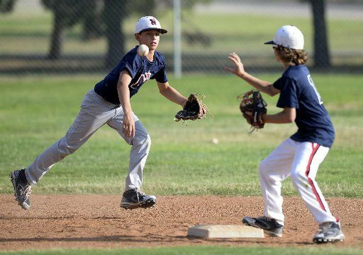 Northern 11-12 year old All-Star Gage Jordan passes the ball to Rhett Clark at second base during a double play drill Wednesday, July 22, 2015 at Butler Park.