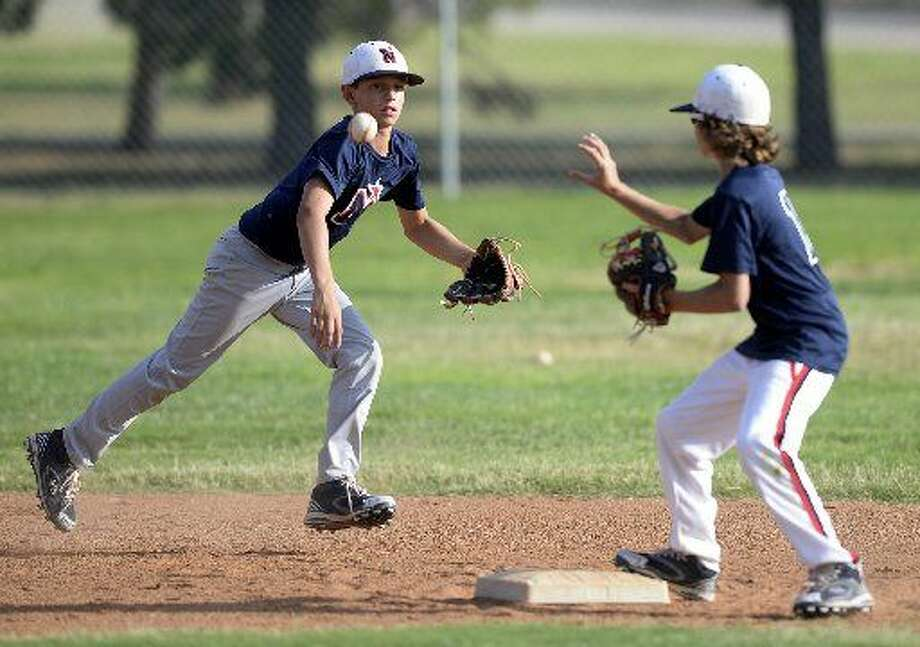 Northern 11-12 year old All-Star Gage Jordan passes the ball to Rhett Clark at second base during a double play drill Wednesday, July 22, 2015 at Butler Park. Photo: James Durbin/Reporter-Telegram