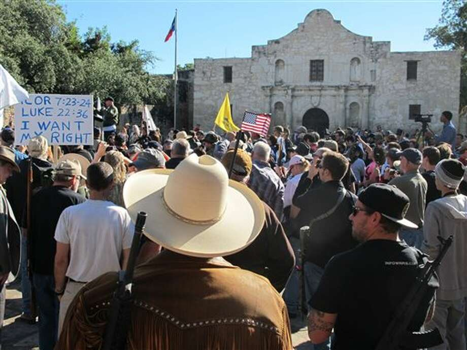 (File Photo) Gun rights advocates gather at the Alamo in San Antonio, Texas on Oct. 19, 2013 to demonstrate in support of a Texas law that permits the open carry of long arms, such as rifles and shotguns. Organizers said a local ordinance restricting the carrying of firearms in public conflicts with state law. (AP Photo/Christopher Sherman) Photo: Christopher Sherman / AP