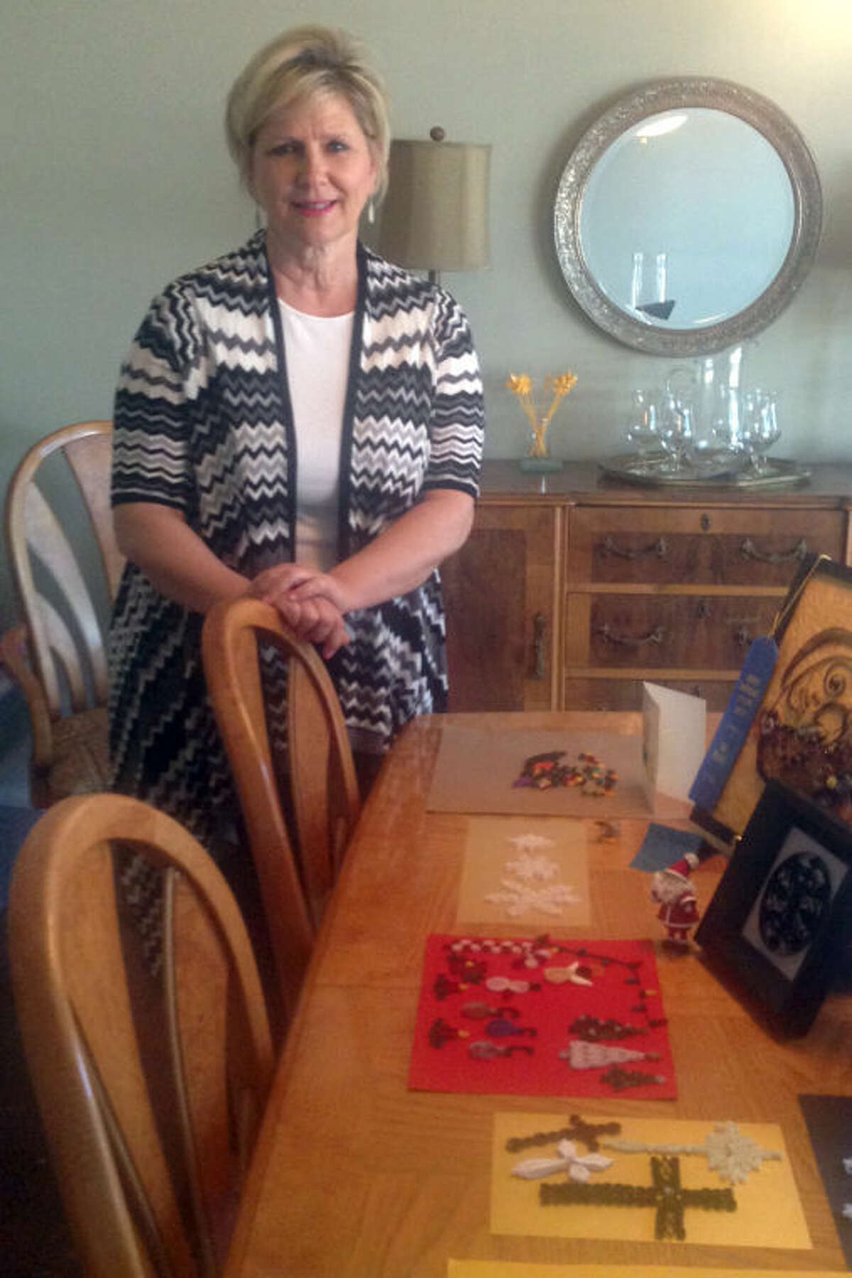 Beth Clark stands with some of the pieces she has quilled in the past 18 months since she took up the paper craft.
