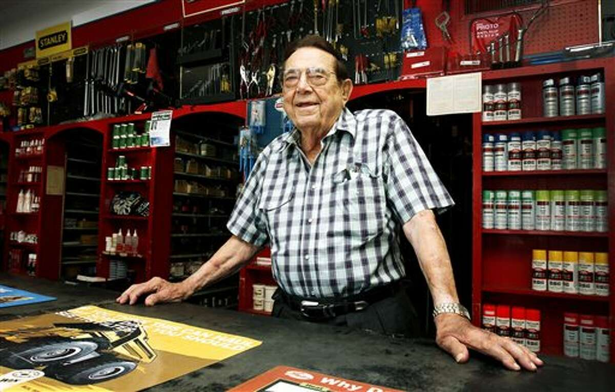 """In this photo taken on Tuesday, June 3, 2014, Edward Kalinowski, 97, smiles behind the counter at Victoria Bearing & Industrial Supply in Victoria, Texas. Kalinowski has been a part of the family business since he was just 13-years-old. He said Victoria Bearing & Industrial is still run as a family owned, local store. Their employees live locally, spend locally and are treated like family. He wants his employees to be happy an healthy at work. """"I always tell them, it don't cost nothing to smile."""" he said. (AP Photo/The Victoria Advocate, Kathleen Duncan)"""
