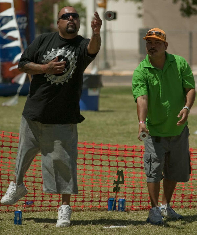 Danny Sanchez. left, and Gilbert Lujan compete in the Huacha/Washer Tournament Saturday at Mex Tex. Tim Fischer\Reporter-Telegram