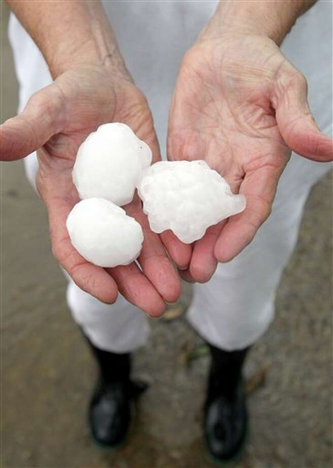 Melba Baker holds some of the golf ball plus size hail that fell at her home in Cunningham, Texas, Tuesday, April 3, 2012. Two large super cell thunderstorms brought heavy rain and damaging winds to North East Texas as well as tornadoes in the Dallas and Fort Woth area. (AP Photo/The Paris News, Sam Craft) Photo: Sam Craft / The Paris News