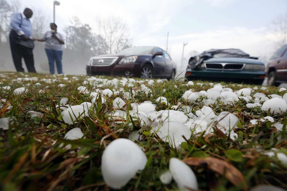 Golfball sized hail litter the ground by Andrew Stamps and his wife Valorie as they prepare to cover their shattered rear window of her 2009 Toyota Avalon in Pearl, Miss., Monday, March 18, 2013, following a hailstorm that hit communities throughout central Mississippi. The National Weather Service in Jackson says there were a few super cells in central Mississippi and reports of hail up to baseball size in Clinton, golf ball and tennis ball sized in Pearl and Brandon and quarter sized in downtown Jackson, Miss. (AP Photo/Rogelio V. Solis)
