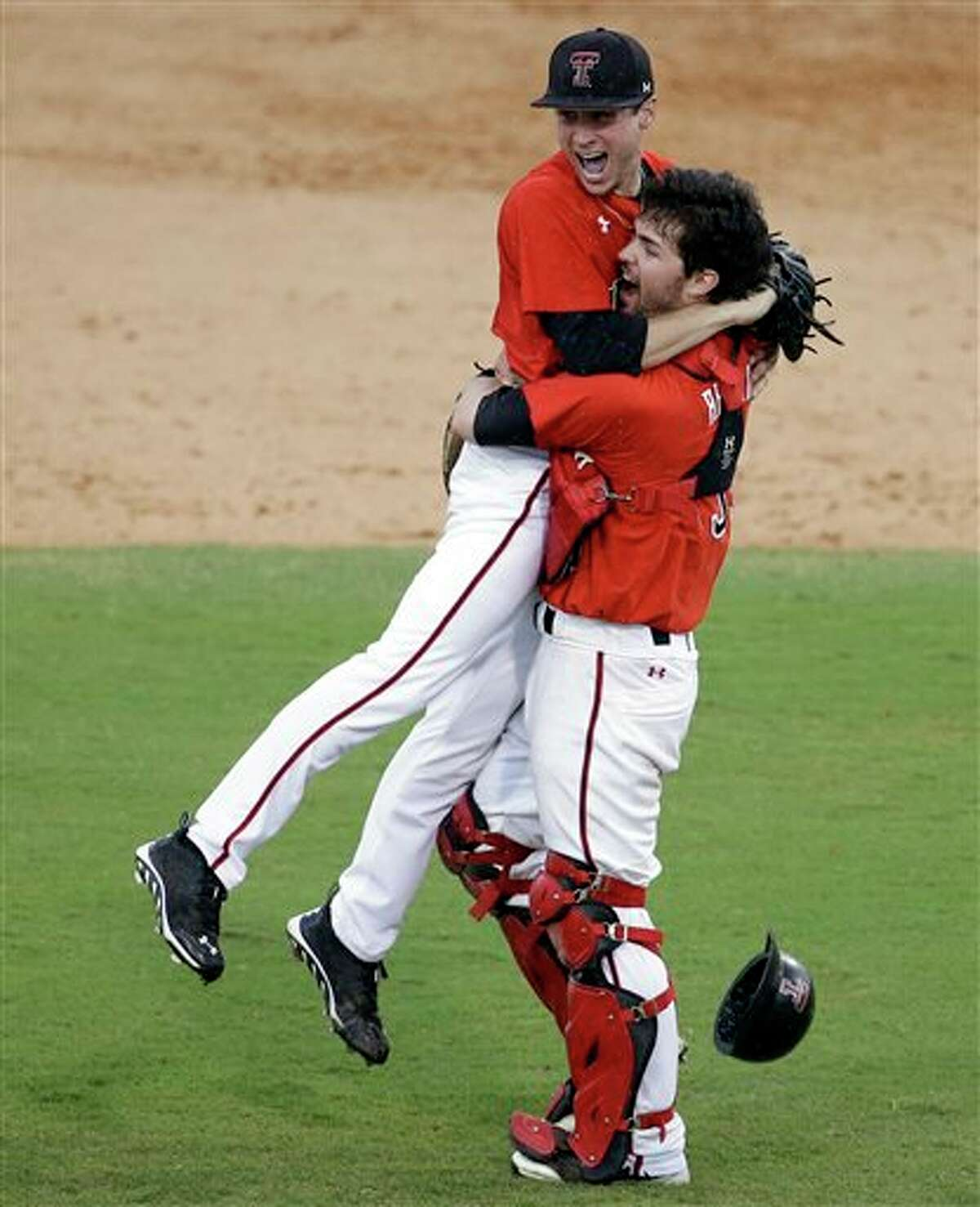 Texas Tech starting pitcher Cameron Smith, left, jumps into the arms of catcher Hunter Redman, right, after defeating Miami 4-0 during an NCAA college baseball regional tournament in Coral Gables, Fla., Monday, June 2, 2014. Texas Tech advances to the Super Regionals with the win. (AP Photo/Lynne Sladky)