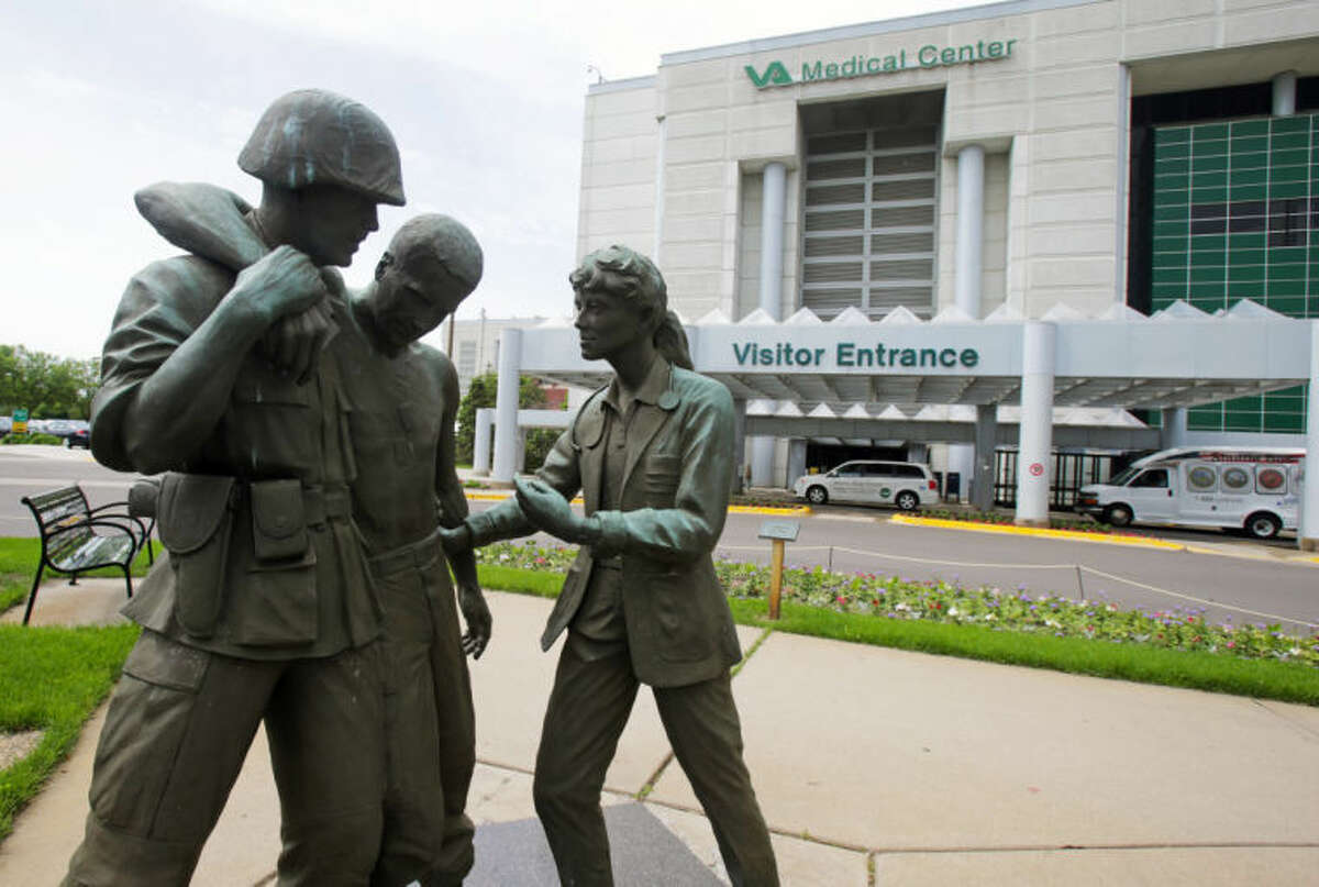 Three statues portraying a wounded soldier being helped, stand on the grounds of the Minneapolis VA Hospital, Monday, June 9, 2014. An audit of 731 VA hospitals and clinics found that a 14-day goal for seeing first-time patients was unattainable given increasing demand for health care. The VA said Monday it was abandoning the scheduling goal. (AP Photo/Jim Mone)