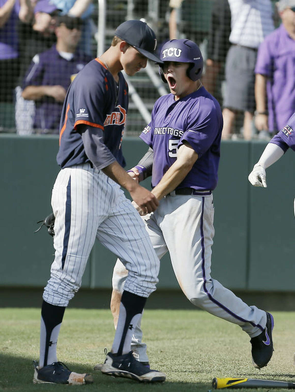 Pepperdine pitcher A.J. Puckett, left, looks on as TCU's Derek Odell (5) celebrates scoring on teammate Kevin Cron's RBI double during the sixth inning of an NCAA college baseball tournament super regional game in Fort Worth, Texas, Monday, June 9, 2014. TCU won 6-5. (AP Photo/Brandon Wade)