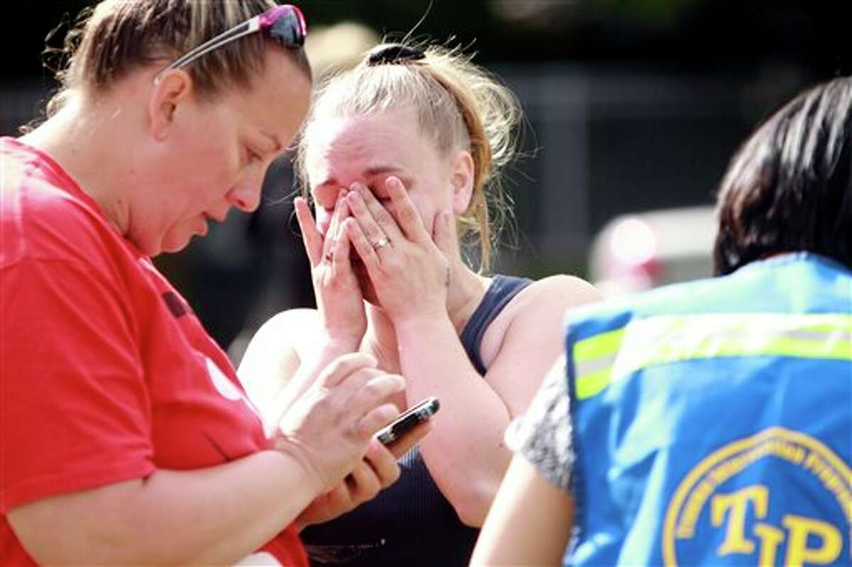A person wipes away tears as they await to hear about the safety of students after a shooting at Reynolds High School Tuesday, June 10, 2014, in Troutdale, Ore. A gunman killed a student at the high school east of Portland Tuesday and the shooter is also dead, police said. (AP Photo/The Oregonian, Faith Cathcart) MAGS OUT; TV OUT; LOCAL TV OUT; LOCAL INTERNET OUT; THE MERCURY OUT; WILLAMETTE WEEK OUT; PAMPLIN MEDIA GROUP OUT