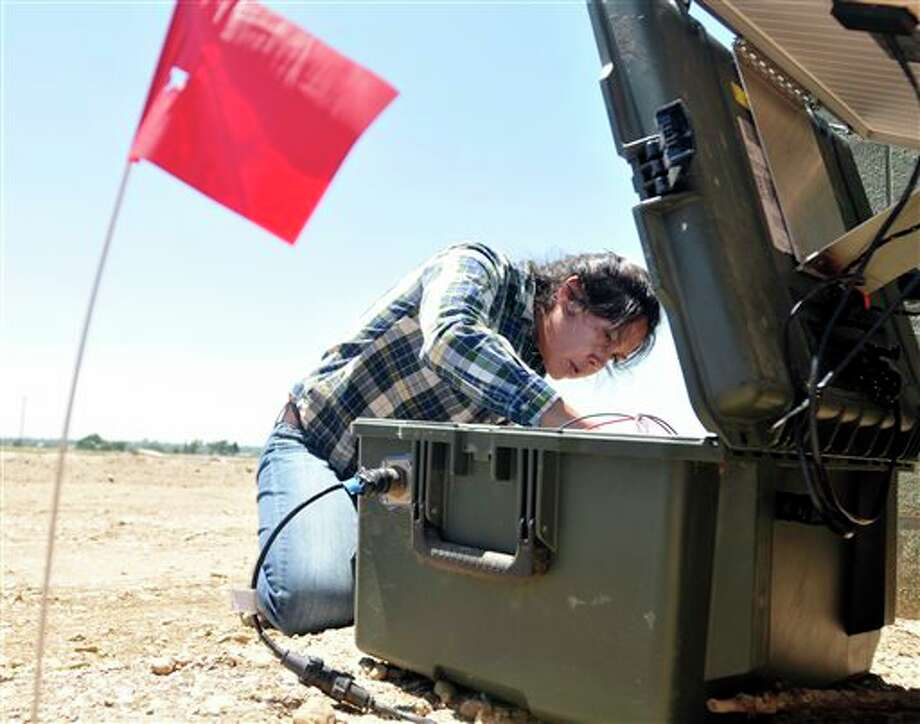 In this June 5, 2014 photo, a red flag marks the seismic monitor buried in the ground as Jenny Nakai, a graduate student in seismology from University of Colorado at Boulder, begins checking one of the instruments above near the intersection of Weld County Road 64 south of Lucerne, Colo. Anne Sheehan, a geophysicist from the University of Colorado is hoping to settle the question of whether a small earthquake last weekend near Greeley was caused by wastewater injection wells. (AP Photo/The Greeley Tribune, Joshua Polson) Photo: Joshua Polson / The Greeley Tribune