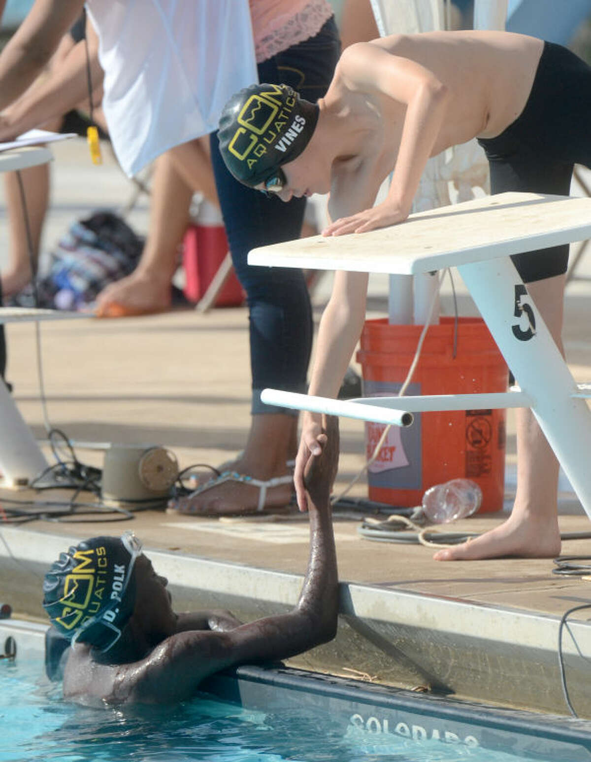D'Avante Polk of COM is congratulated by a teammate after taking first place in the Boys 11-12 400 Free event during the 69th annual Frost Bank Invitational on Thursday at Doug Russell Pool. James Durbin/Reporter-Telegram