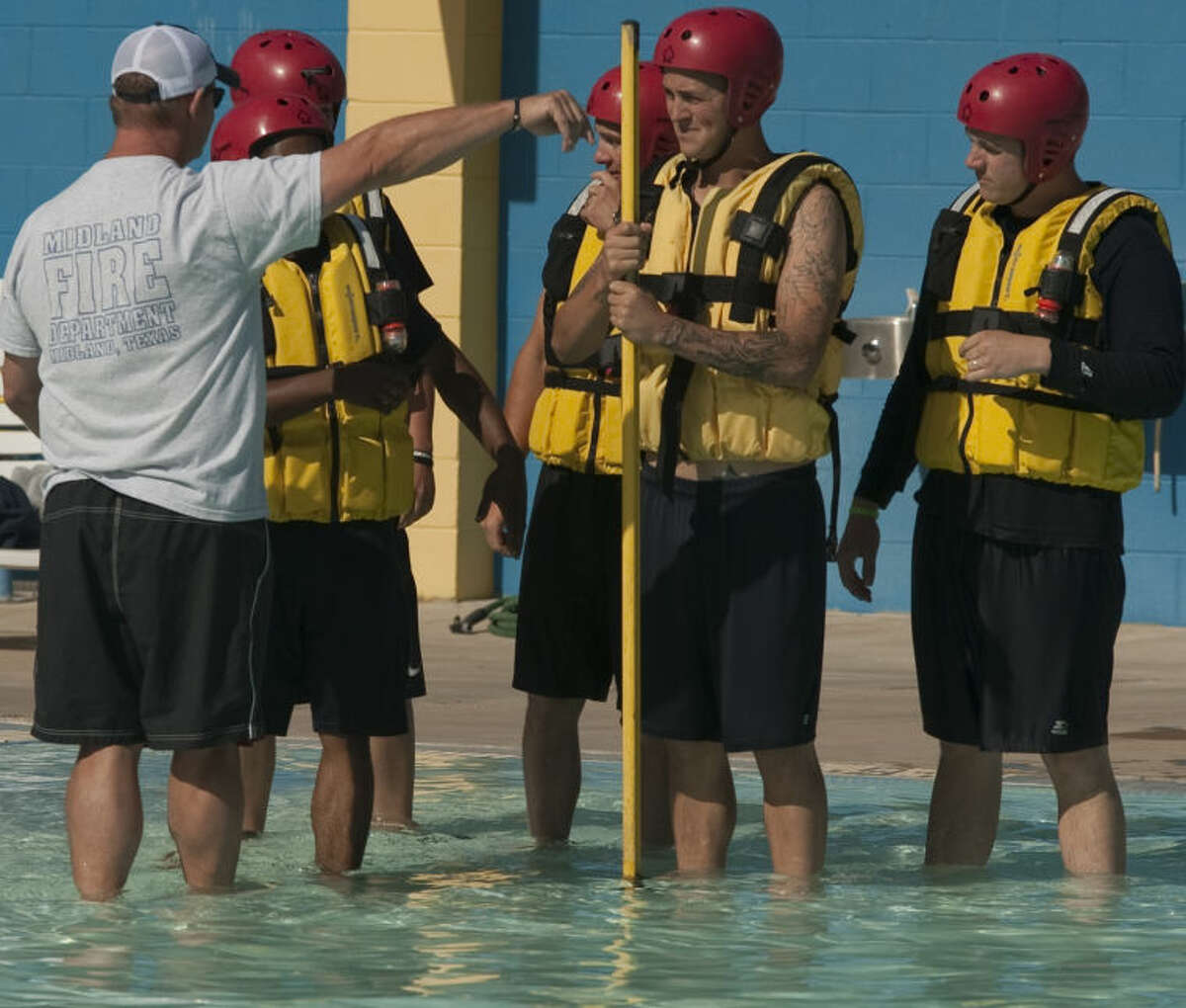 MFD firefighter Rusty Welch works with recruits on safety measures during water rescues Thursday at Washington Pool. Tim Fischer\Reporter-Telegram