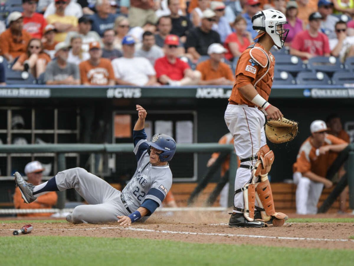 UC Irvine shortstop Chris Rabago (22) scores on a single by Jonathan Munoz in the eighth inning of an NCAA baseball College World Series game against Texas in Omaha, Neb., on Saturday. At right is Texas catcher Tres Barrera. (AP Photo/Ted Kirk)