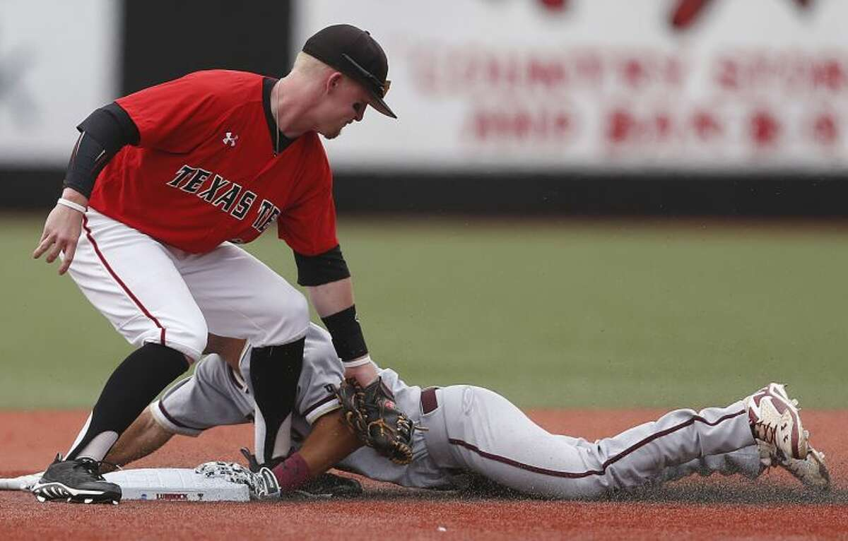 College of Charleston's Champ Rowland slides safely into second base ahead of the tag by Texas Tech's Bryant Burleson, left, during a NCAA college baseball tournament super regional game in Lubbock, Texas, Saturday, June 7, 2014. (AP Photo/Lubbock Avalanche Journal, Shannon Wilson)
