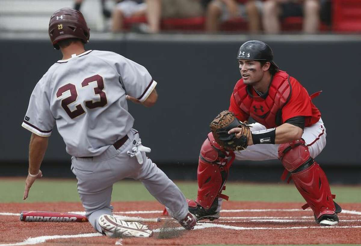 Texas Tech's Hunter Redman, right, prepares to tag out the College of Charleston's Brandon Glazer (23) at home plate during a NCAA college baseball tournament super regional game in Lubbock, Texas, Saturday, June 7, 2014. (AP Photo/Lubbock Avalanche Journal, Shannon Wilson)