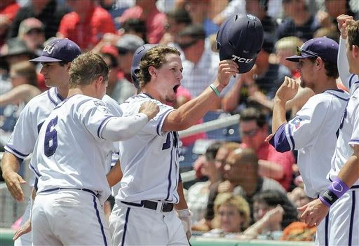 TCU's Cody Jones, center, celebrates with teammates after scoring against Texas Tech on a sacrifice fly hit by teammate Boomer White in the first inning of an NCAA baseball College World Series game in Omaha, Neb., Sunday, June 15, 2014. (AP Photo/Eric Francis)