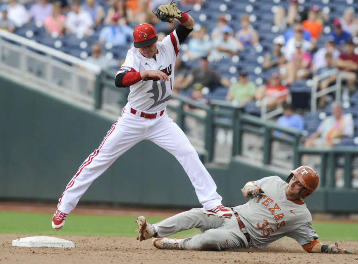 Texas' Madison Carter (35) slides safely to second base under Louisville shortstop Sutton Whiting (1) on a single by Kacy Clemens and a throwing error in the ninth inning of an NCAA baseball College World Series elimination game in Omaha, Neb., Monday, June 16, 2014. Texas won 4-1. (AP Photo/Eric Francis)