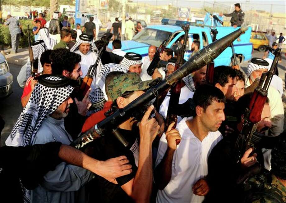 In this Tuesday, June 17, 2014 photo, Iraqi Shiite tribal fighters raise their weapons and chant slogans against the al-Qaida-inspired Islamic State of Iraq and the Levant, after authorities urged Iraqis to help battle insurgents, in Baghdad's Sadr city, Iraq. Thousands of Shiites from Baghdad and across southern Iraq answered an urgent call to arms Saturday, joining security forces to fight the Islamic militants who have captured large swaths of territory north of the capital and now imperil a city with a much-revered religious shrine. (AP Photo/Karim Kadim) Photo: Karim Kadim / AP