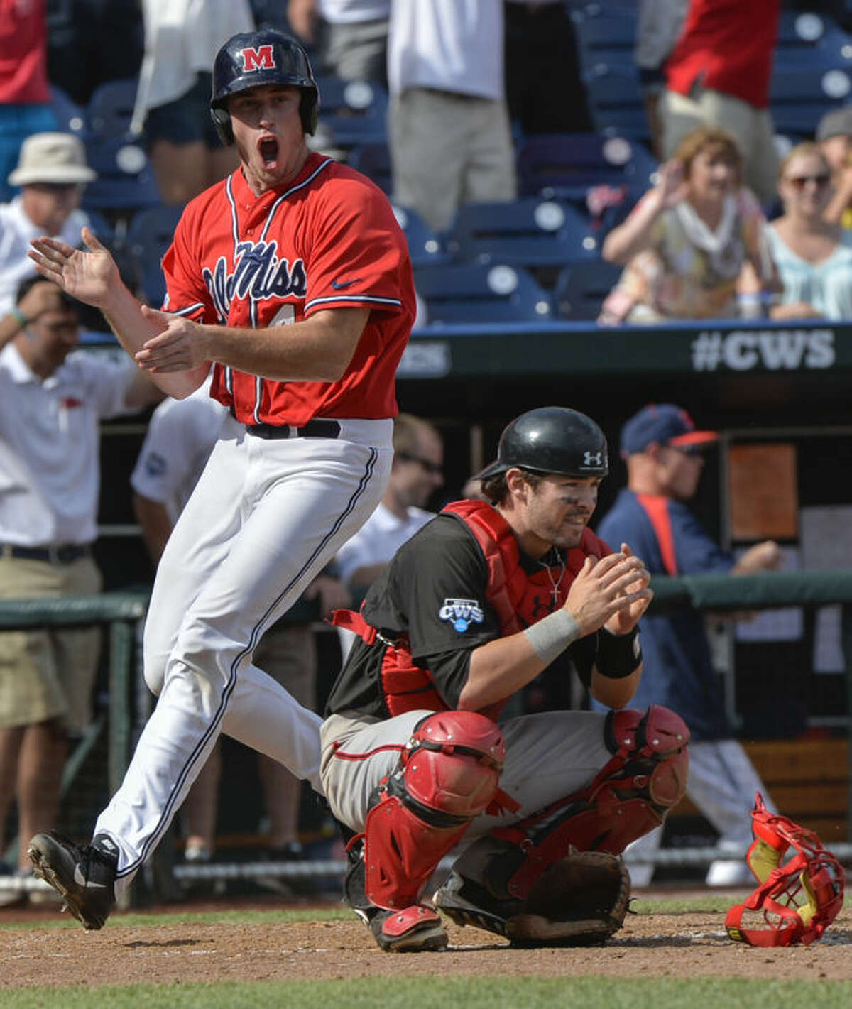 Mississippi's Aaron Greenwood, who scored the winning run against Texas Tech on a single by John Gatlin, celebrates left, as Texas Tech catcher Hunter Redman (5) crouches dejected, following an NCAA baseball College World Series elimination game in Omaha, Neb., Tuesday, June 17, 2014. (AP Photo/Ted Kirk)