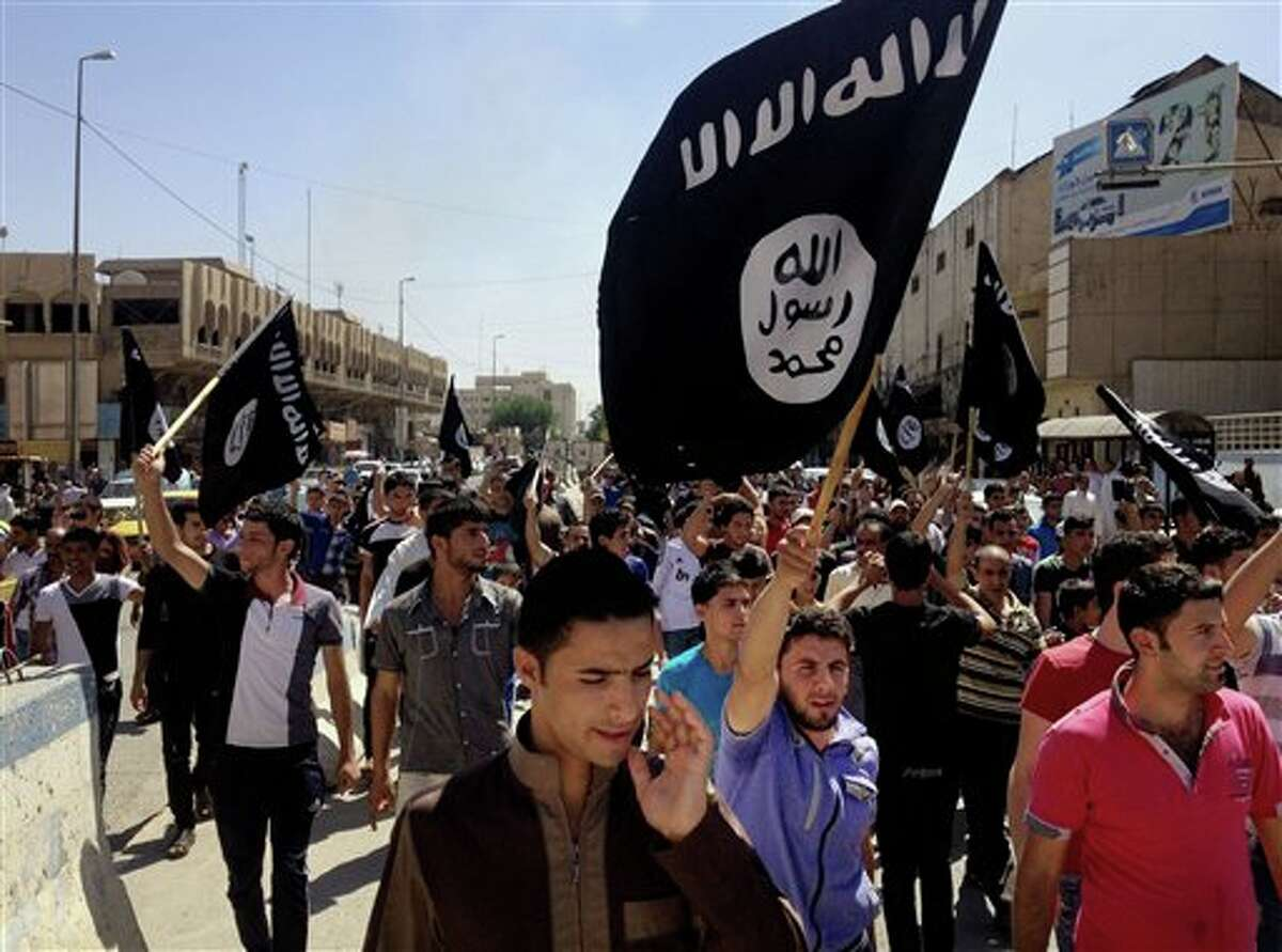 FILE - In this Monday, June 16, 2014 file photo, demonstrators chant pro-al-Qaida-inspired Islamic State of Iraq and the Levant as they carry al-Qaida flags in front of the provincial government headquarters in Mosul, 225 miles (360 kilometers) northwest of Baghdad, Iraq. The CIA and other spy agencies are scrambling to close intelligence gaps as they seek ways to support possible military or covert action against the leaders of the al-Qaida-inspired militant group that has seized parts of Iraq and threatens Baghdad's government. (AP Photo, File)
