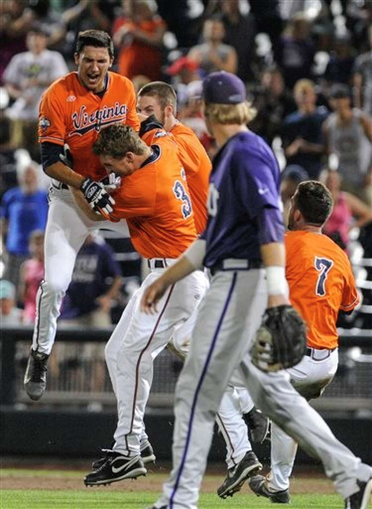 Virginia shortstop Daniel Pinero, left, celebrates with Thomas Woodruff (37) and others after winning 3-2 an NCAA baseball College World Series game against TCU in 15 innings in Omaha, Neb., Wednesday, June 18, 2014. TCU's Kevin Cron is looking on in the foreground. (AP Photo/Eric Francis)