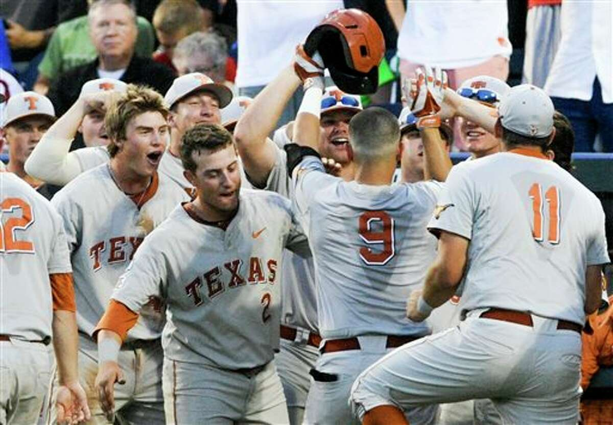 Texas players greet C.J Hinojosa (9) to the dugout after he hit a home run against UC Irvine in the seventh inning of an NCAA baseball College World Series elimination game in Omaha, Neb., Wednesday, June 18, 2014. (AP Photo/Eric Francis)