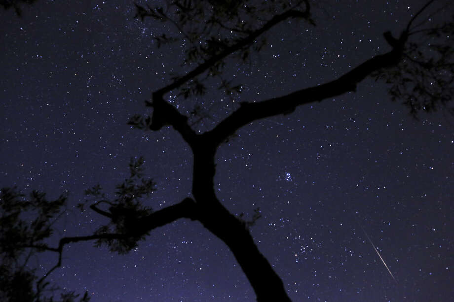 In this photo taken with long shutter speed, a meteor sparks while entering the earth's atmosphere behind an olive tree during the Perseids Meteor Shower, in Fanos village, central Greece, on Saturday, Aug. 10, 2013. The Perseids are a prolific meteor shower associated with the comet Swift-Tuttle. The Perseids shower is visible from mid- July each year, with the peak in activity being between Aug. 9 and 14 depending on the particular location of the stream.(AP Photo/Petros Giannakouris) Photo: Petros Giannakouris