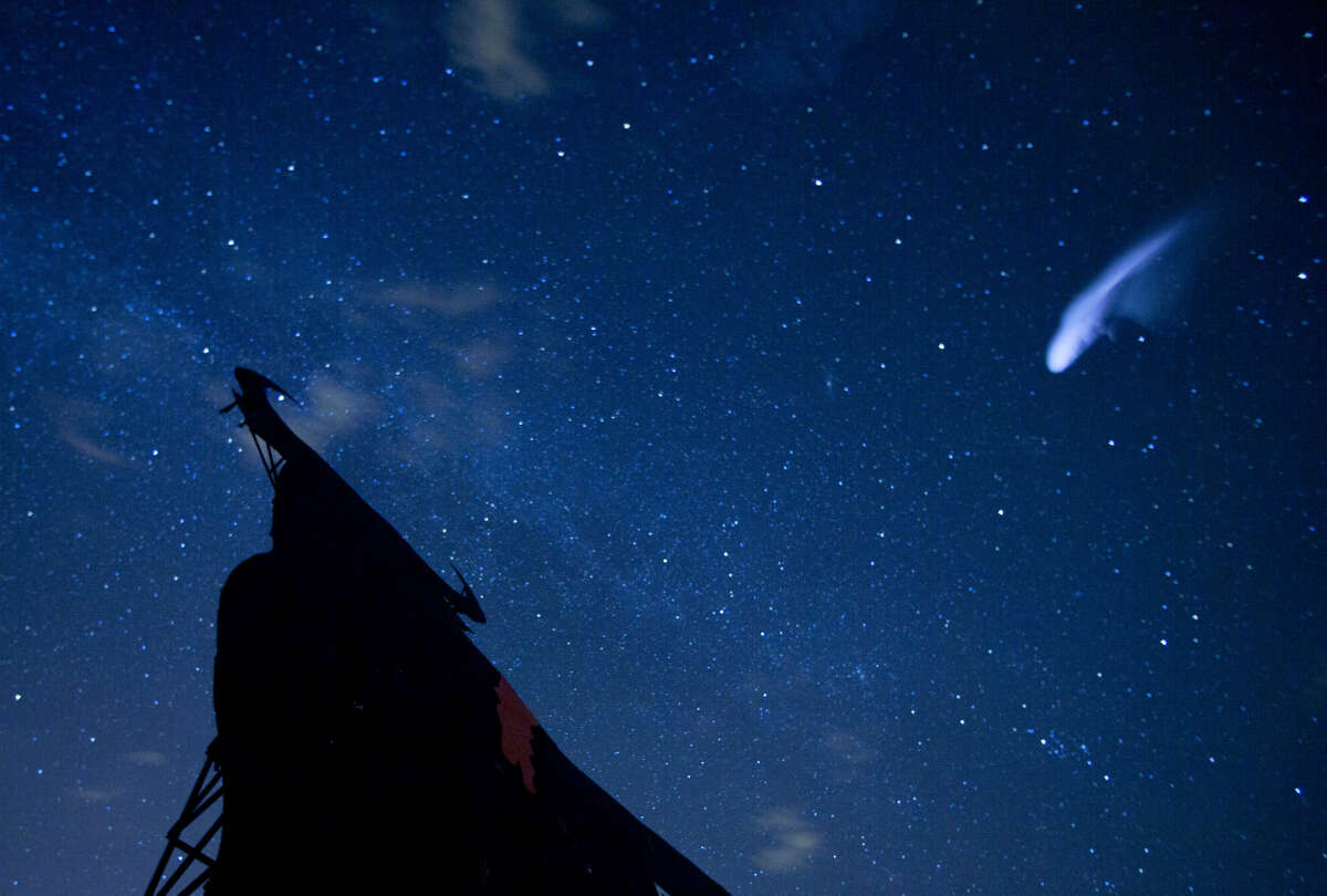 In this long exposure photo, a streak appears in the sky during the annual Perseid meteor shower above a roadside silhouette of a Spanish fighting bull, conceived decades ago in Spain as highway billboards, in Villarejo de Salvanes, central Spain in the early hours of Monday Aug. 12, 2013. (AP Photo/Paul White)