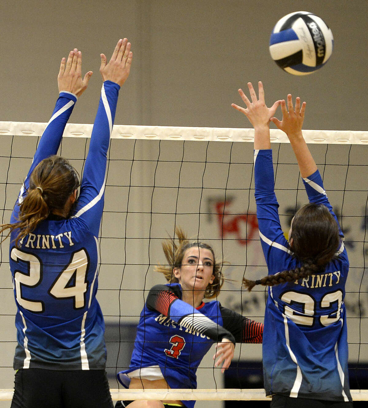 Midland Christian's Kenzie Pullen (3) hits past Trinity's Callie Herd (24) and Hilary Lanier (23) on Tuesday, August 11, 2015 at Beal Gymnasium. James Durbin/Reporter-Telegram