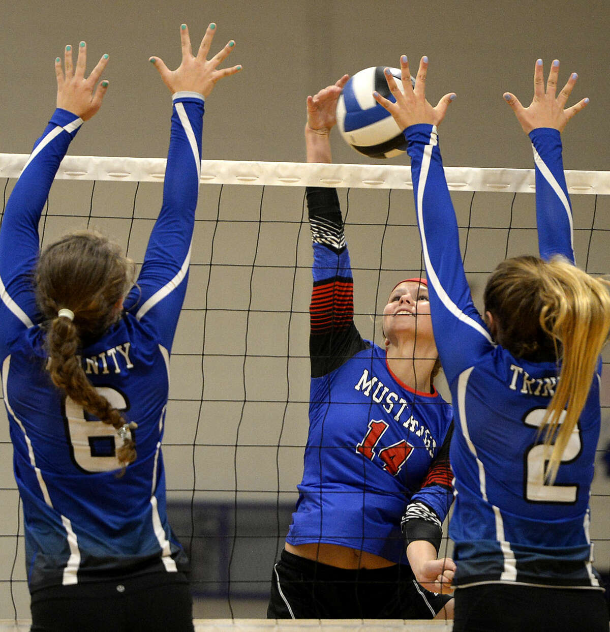 Midland Christian's Meagan Thomason (14) attempts to hit past Trinity's Mady Walker (6) and Carrie Herd (2) on Tuesday, August 11, 2015 at Beal Gymnasium. James Durbin/Reporter-Telegram