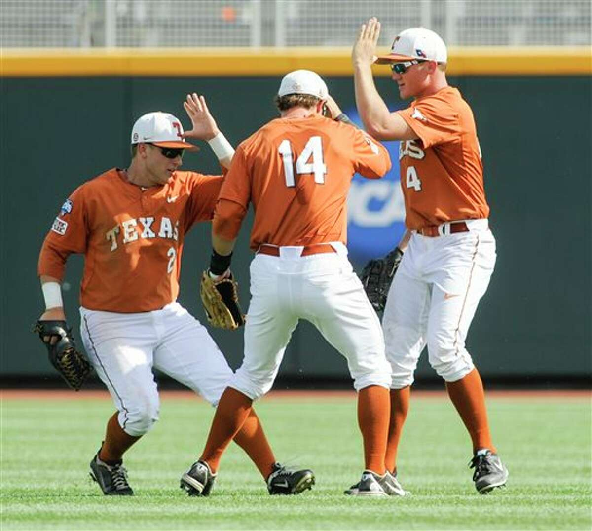 From left to right, Texas' Mark Payton, Ben Johnson and Collin Shaw celebrate after winning 4-0 against Vanderbilt in an NCAA baseball College World Series game in Omaha, Neb., Friday, June 20, 2014. (AP Photo/Eric Francis)