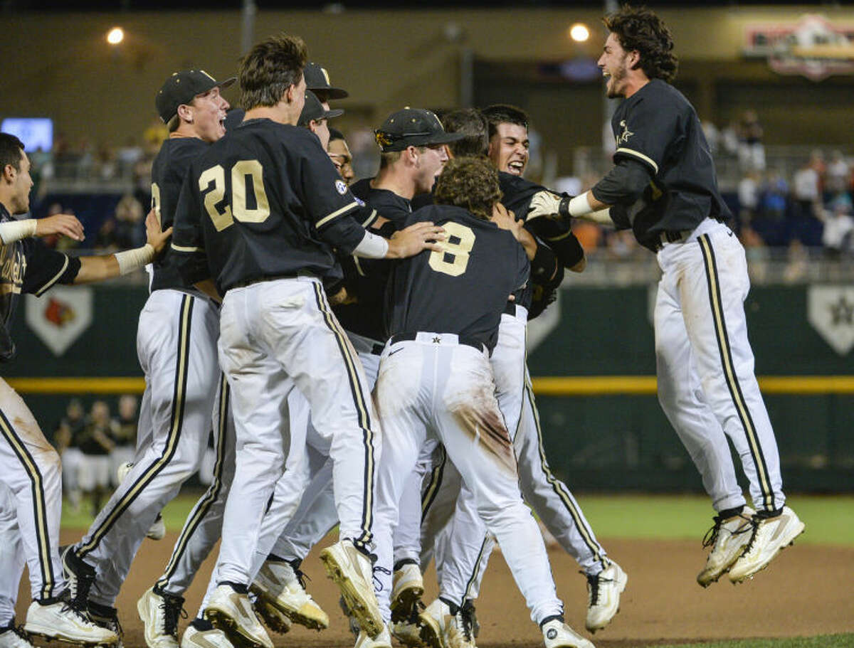 Vanderbilt players celebrate after an infield single by Tyler Campbell in the 10th inning scored Rhett Wiseman for a 4-3 win over Texas in an NCAA baseball College World Series game in Omaha, Neb., on Saturday. Vanderbilt advances to the championship series. (AP Photo/Ted Kirk)