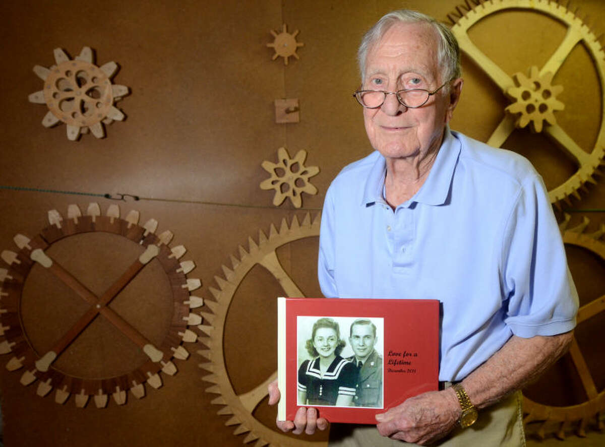 John Crosby - World War II veteran - John Crosby poses with some handmade clock gears he built holding a photo album depicting his late wife, Mary, on Thursday at his home. James Durbin/Reporter-Telegram