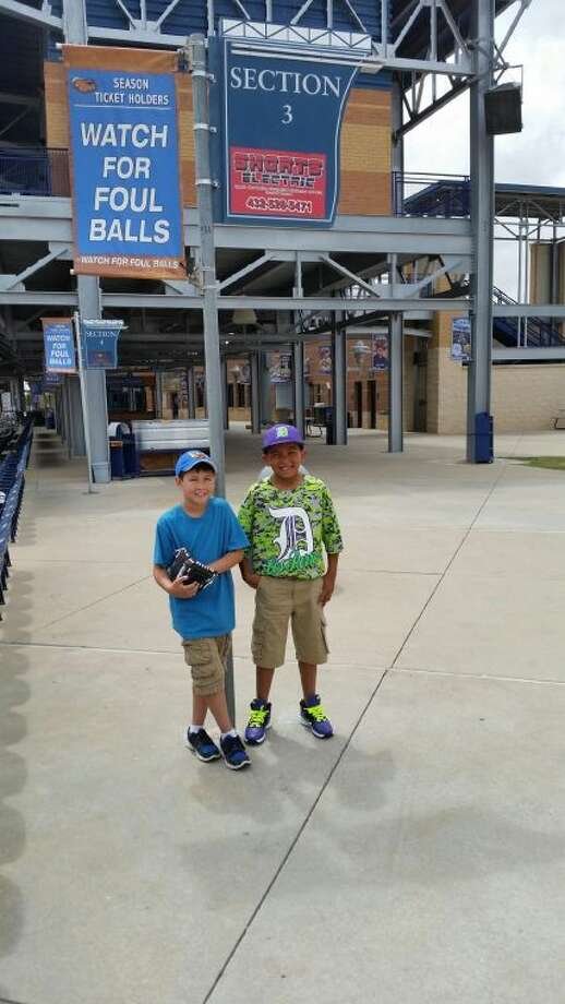 Nicolas Pettit and A.D. Navarro Jr. pose for a picture at a recent RockHounds game. When Pettit was hit in the face by a foul ball, Navarro spent his own money on a souvenir ball for him. Photo: Courtesy Photo