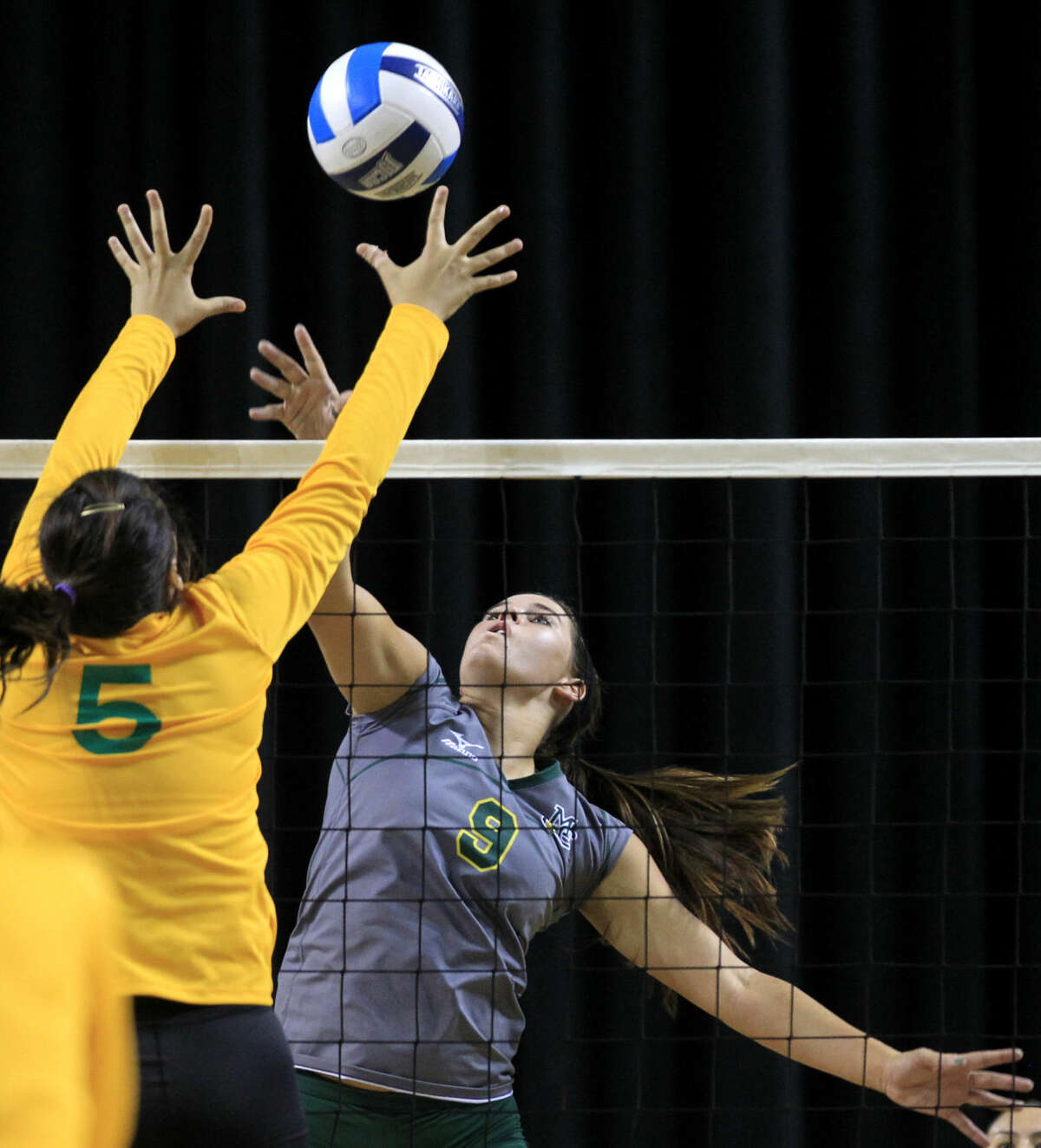 Midland College's Shelby Bartley (9) hits against Laredo's Stephanie Perez (5) on Saturday, Aug. 23, 2014 at Chaparral Center. James Durbin/Reporter-Telegram