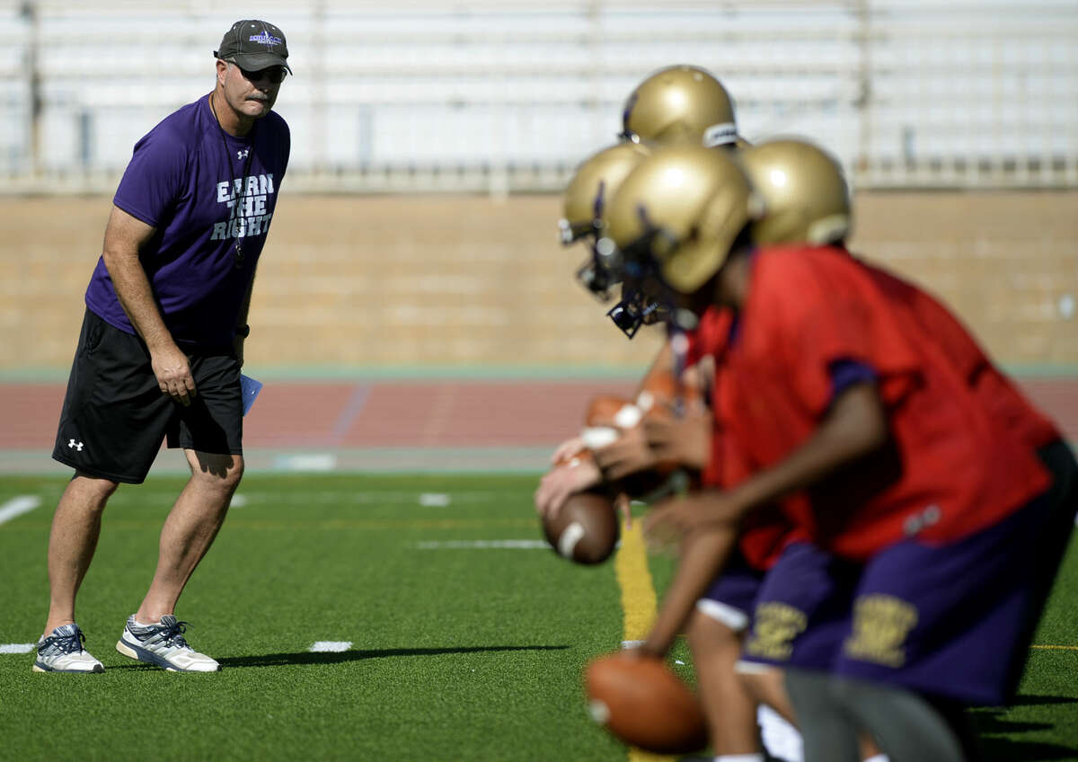 Midland High head football coach Craig Yenzer works with quarterbacks at the first team practice of the season Monday, August 10, 2015 at Memorial Stadium. James Durbin/Reporter-Telegram