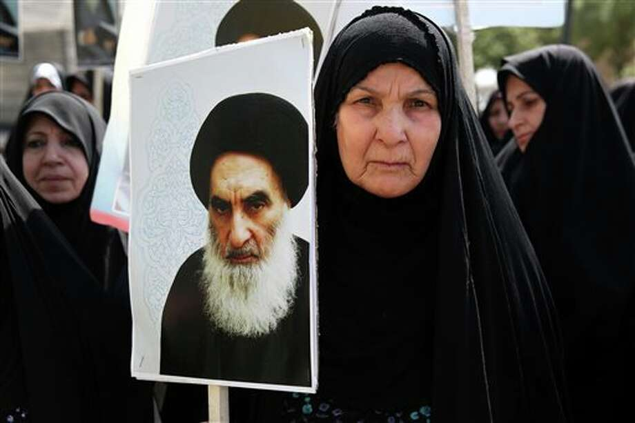 FILE - In this June 20, 2014 file photo, an Iraqi woman living in Iran holds a poster of the Grand Ayatollah Ali al-Sistani, Iraq's top Shiite cleric, in a demonstration against Sunni militants of the al-Qaida-inspired Islamic State of Iraq and the Levant, or ISIL, and to support Ayatollah al-Sistani, in Tehran, Iran. Prominent Shiite leaders pushed Thursday, June 26, 2014, for the removal of Iraqi Prime Minister Nouri al-Maliki as parliament prepared to start work next week on putting together a new government, under intense U.S. pressure to rapidly form a united front against an unrelenting Sunni insurgent onslaught. (AP Photo/Ebrahim Noroozi, File) Photo: Ebrahim Noroozi / AP