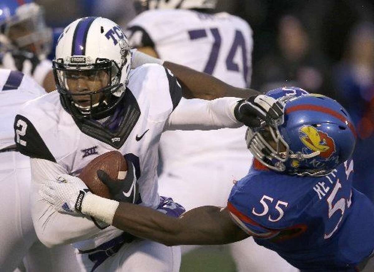 FILE - In this Nov. 15, 2014, file photo, TCU quarterback Trevone Boykin (2) avoids a tackle by Kansas linebacker Michael Reynolds (55) during the second half of an NCAA college football game in Lawrence, Kan. TCU coach Gary Patterson and Baylor coach Art Briles know a nearly-sure-fire way for their teams, and the Big 12 Conference, to avoid being left out of the College Football Playoff again.