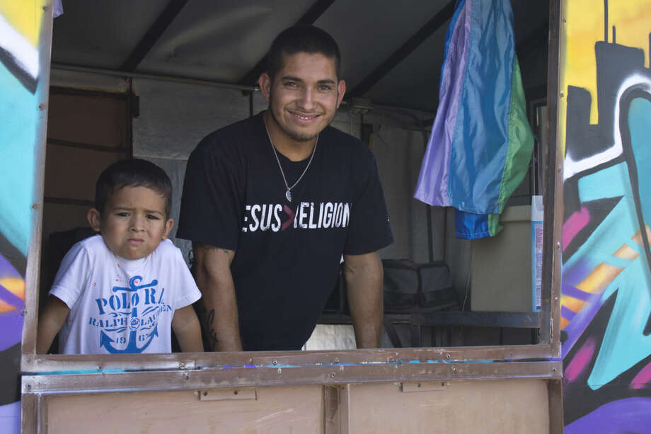 Mark Barraza with his son Daniel inside his mobile 'Church in the Hood.' Photo: Trent Johnson/Midland Reporter-Telegram